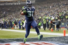 Seahawks safety Kam Chancellor runs for a touchdown following his interception during the fourth quarter as the Seattle Seahawks face the Carolina Panthers in an NFL Divisional Playoff game at CenturyLink Field on Saturday, January 10, 2015. 144131